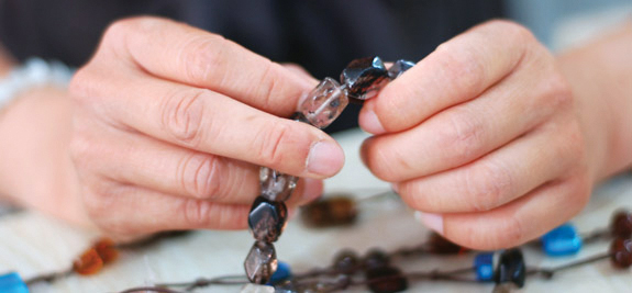 image of womans hands making jewelry